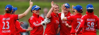 The England women's team celebrate a wicket by Natalie Sciver (centre)