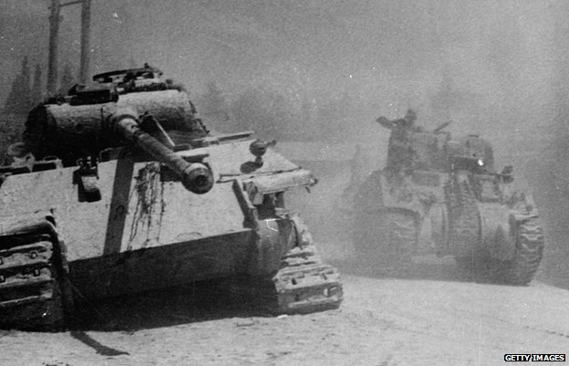 July 1944 - An allied Sherman tank passing a knocked out German Panther tank during the advance on Arezzo, Italy