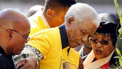 Former South African President Nelson Mandela (centre) is helped as he walks up the stairs by then-current ANC president and presidential candidate Jacob Zuma (left), his former wife Winnie (right) and his grandson Mandla (behind) at the start of an ANC rally in Johannesburg, South Africa [19 April 2009]