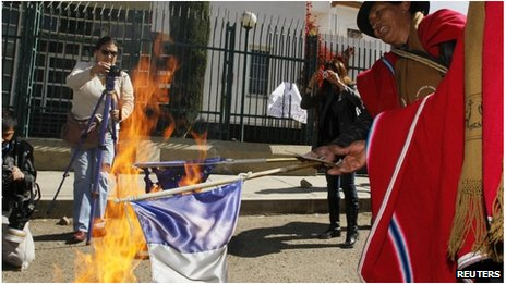 Bolivian protester burning French flag in La Paz
