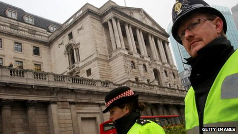 Police walk past the Bank of England