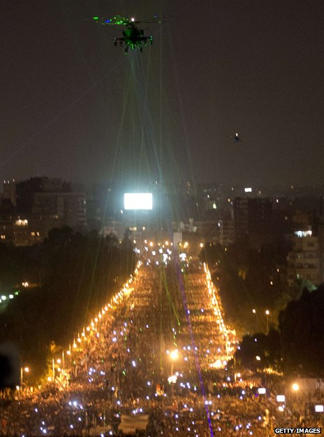 Helicopter flying above Cairo, picked out by laser pens