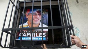 Supporters of Venezuelan opposition presidential candidate Henrique Capriles have a poster with his picture at their home in the Petare slum in Caracas on April 13