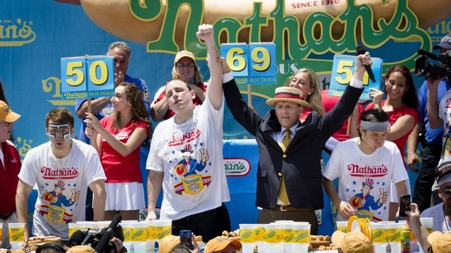 Joey Chestnut, (c), wins the hot dog eating contest