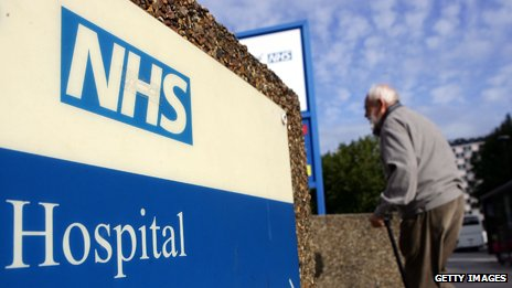 An elderly man walks past an NHS sign