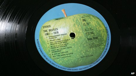 A Beatles vinyl with their whole green apple logo