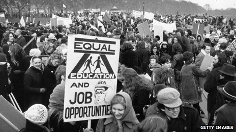 "A woman holds an ""Equal education and job opportunities"" sign at a Women's Liberation Movement demonstration in 1971"