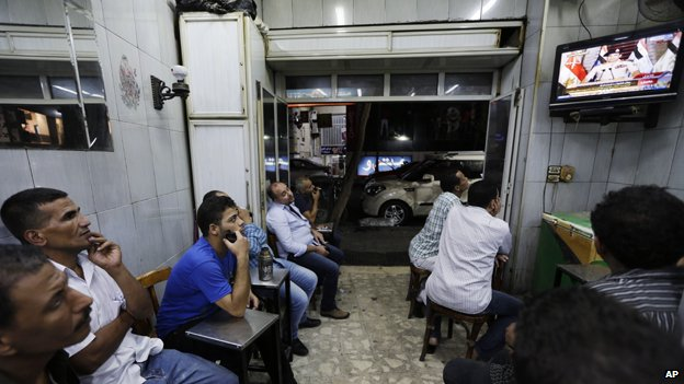 Egyptians watch Defense Minister Gen Abdul Fattah al-Sisi's announcement on TV at a tea house in Cairo