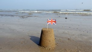 Sand castle and union flag on beach (Image: BBC)