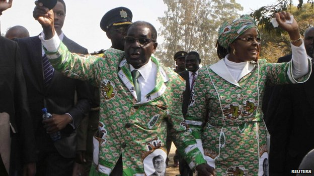 Zimbabwean President Robert Mugabe (L) and his wife Grace wave to party supporters on his arrival to launch of Zanu-PF's election campaign, 5 July 2013