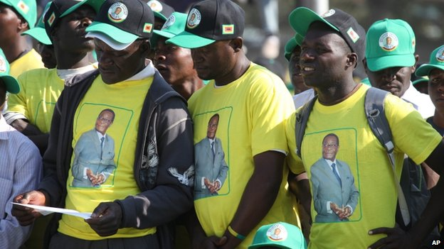 Zimbabwean President Robert Mugabe supporters read campaign material during Mugabe's speech at the launch of his party election campaign in Harare Friday 5 July 2013