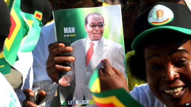 A Zanu-PF supporter holds a programme with a portrait of Zimbabwean President Robert Mugabe at the launch of the party's election campaign in Harare, Friday 5 July 2013