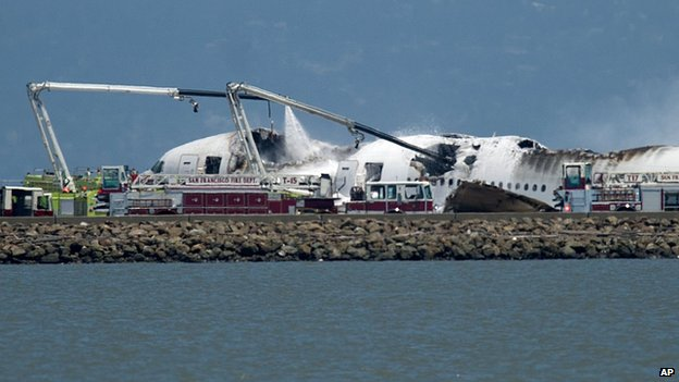 A fire engine sprays water on Asiana Flight 214 after it crashed at San Francisco International Airport on 6 July 2013