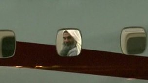Abu Qatada looking out of a plane window