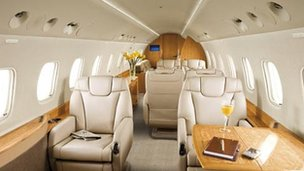 The inside of a private jet, with plush cream-coloured seats