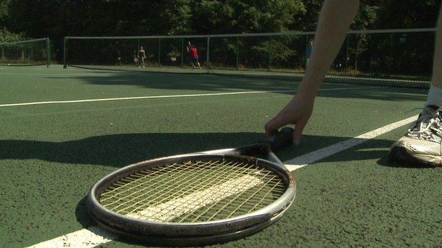 Man picking up tennis racquet