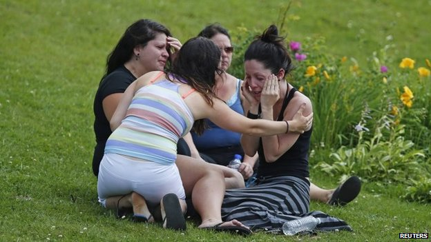 A woman comforts her friend outside the Polyvalente Montignac, the school sheltering people who were forced to leave their homes after the explosion, in Lac-Megantic, 7 July 2013