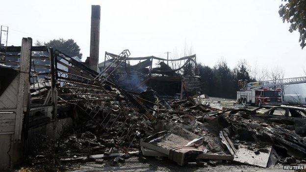 Burned-out buildings are seen near the wreckage of the train derailment in Lac-Megantic, 7 July 2013