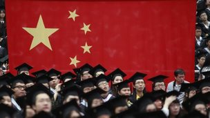 Graduates next to the Chinese flag during a graduation ceremony at Fudan University in Shanghai, 28 June 2013
