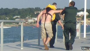 Injured yachtsman being helped to ambulance