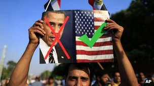 An opponent of Egypt's Islamist President Mohammed Morsi holds up a picture showing the United States President Barack Obama and US flag during a rally outside the Presidential palace in Cairo, Egypt, 7 July 2013