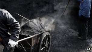 Chinese worker pulls a cart full of coal to deliver them to a heating station. File photo
