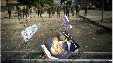 Morsi poster in barbed wire barricade at Republican Guard barracks in Cairo (9 July 2013)