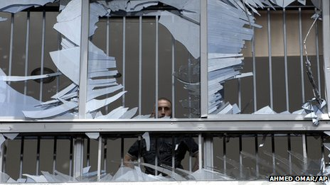 Man looks out from broken window in Beirut
