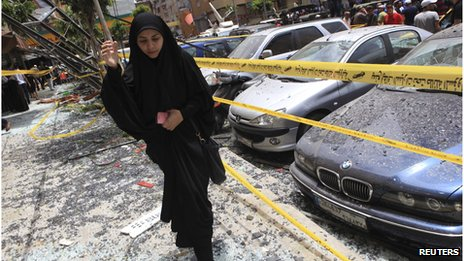 A woman walks over shattered glass, past damaged cars near the site of an explosion in Beirut's southern suburbs