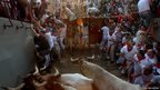Runners against the gates of the bull ring during the third running of the bulls at the San Fermin festival in Pamplona