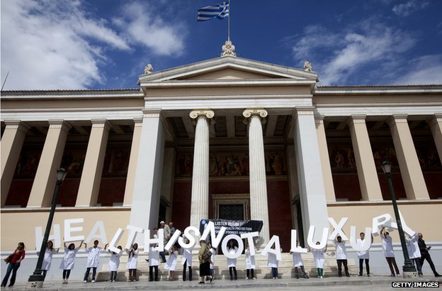 Members of the French medical charity Medecins du Monde (MDM, Doctors of the world) hold letters reading 'health is not a luxury ' outside the University of Athens