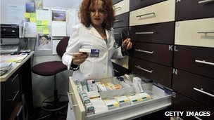 A pharmacisit looks for a prescription drug at her pharmacy in Athens