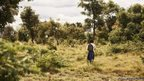 Tanzanian schoolgirl Sylvia walking through the bush