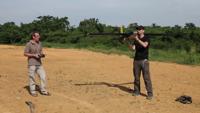 Two men about to fly a drone aircraft in Sumatra