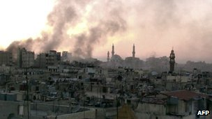 Smoke rises from buildings in Homs after government air strikes on 9 July 2013