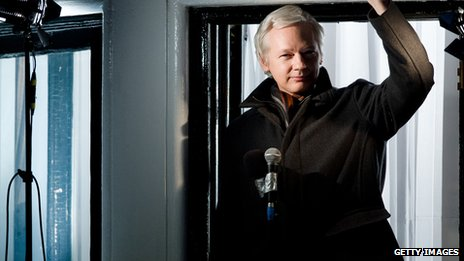 Julian Assange standing at the Ecuadorean embassy