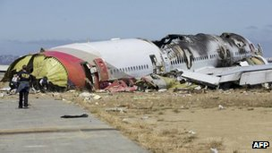 An NTSB investigator looking at the fuselage of Asiana Flight 214, 7 July 2013