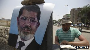 Morsi supporter reads Koran on barrier erected near sit-in