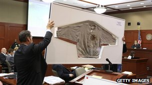 Assistant state attorneys John Guy (L) and Richard Mantei hold up Trayvon Martin's sweatshirt as evidence during George Zimmerman's trial 25 June 2013