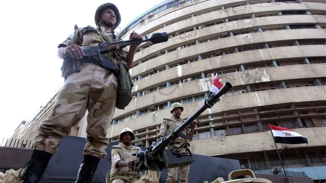 Soldiers outside the state-run television station in Cairo on 6 July 2013