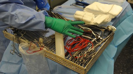 Gloved hand arranging tray of surgical instruments