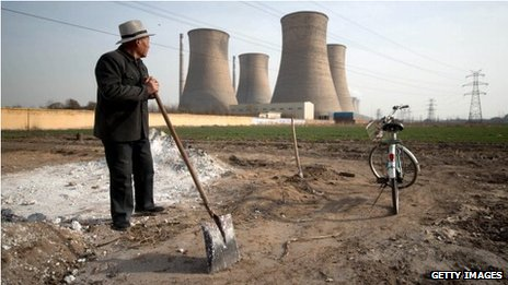 Man looking towards power station chimney stacks in Zingtai