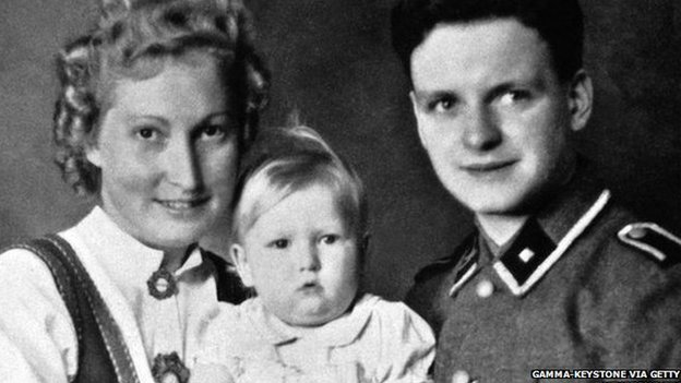 These German parents hold an allegedly 'Aryan' girl  who was born in a centre for eugenics during WWII