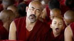 A young Tibetan Buddhist monk yawns
