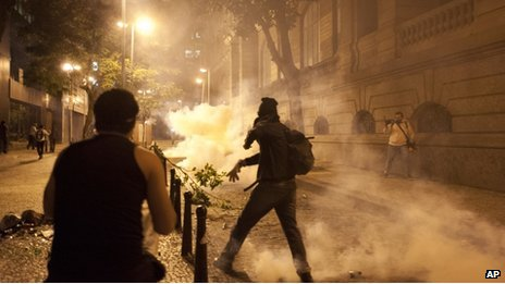 A demonstrator throws a tear gas canister back at police during a protest in Rio, 11 July