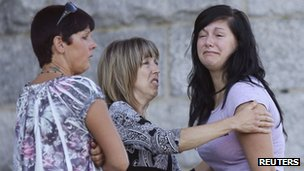 A crying woman is comforted by two others at the Sainte-Agnes Church following the train disaster in Lac-Megantic