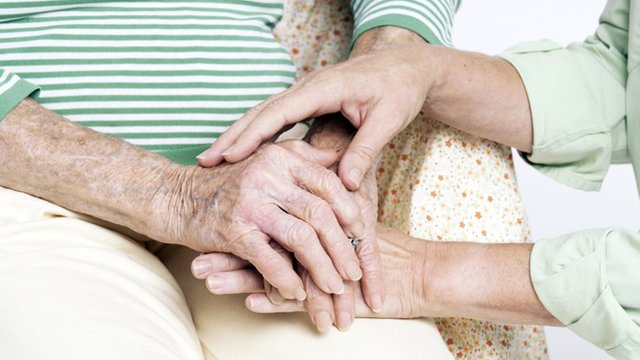 Elderly woman being comforted by a carer who is holding her hands