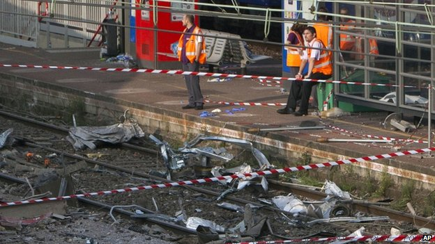 Railway workers look at the scene of the crash in Bretigny-sur-Orge, 13 July 2013