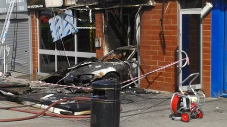 The burnt-out car can be seen inside the club entrance