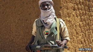 A fighter with the Tuareg separatist group MNLA stands guard outside the local regional assembly